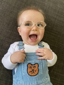 Max smiling wearing glasses in teddy dungarees