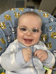 Max smiling in glasses in rocker