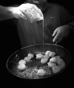 Picture of the chef adding butter to a frying pan of scallops. The final meal is blood orange, Fennel and seared sea scallops on a Sicilian-style salad which is promoting Healthy Eating for Healthy Eyes